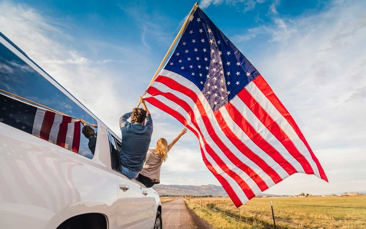 Couple waving American flag out car window