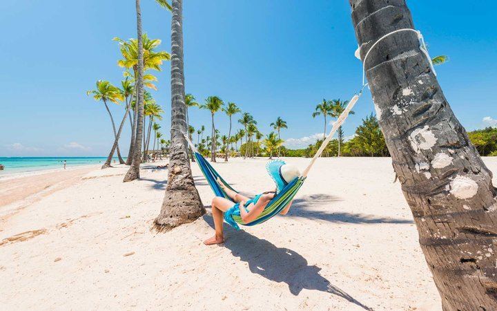 Caucasian woman lying on hammock on a tropical beach.