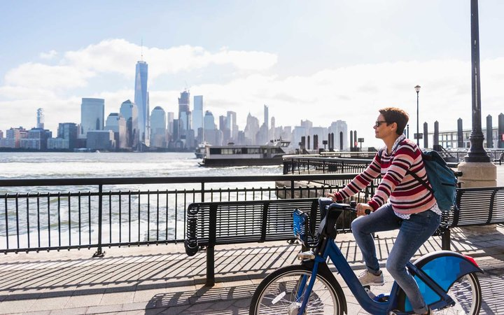 USA, woman on bicycle at New Jersey waterfront with view to Manhattan