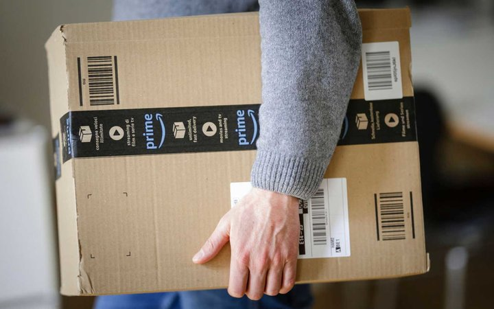A man is holding an Amazon Prime package on March 20, 2018 in Berlin, Germany
