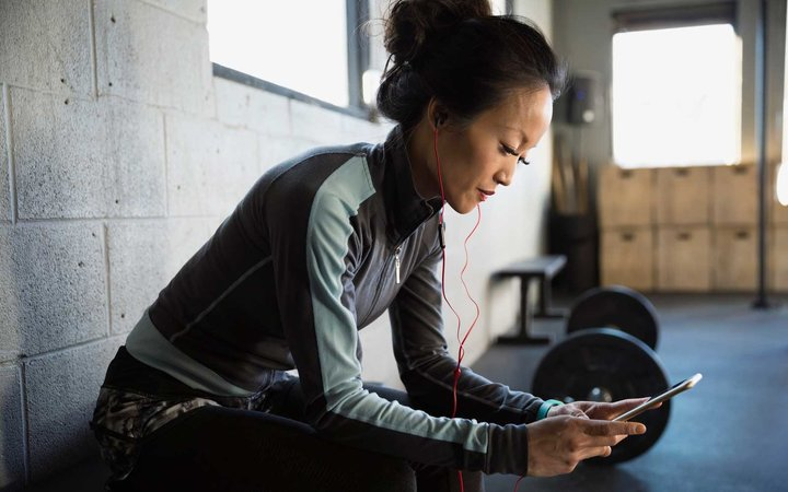 Woman with headphones using cell phone at gym