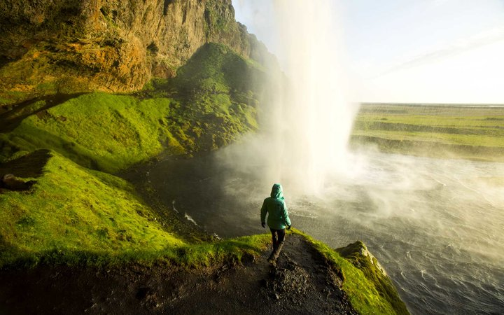 A woman watching the sunset from behind a waterfall in Iceland.