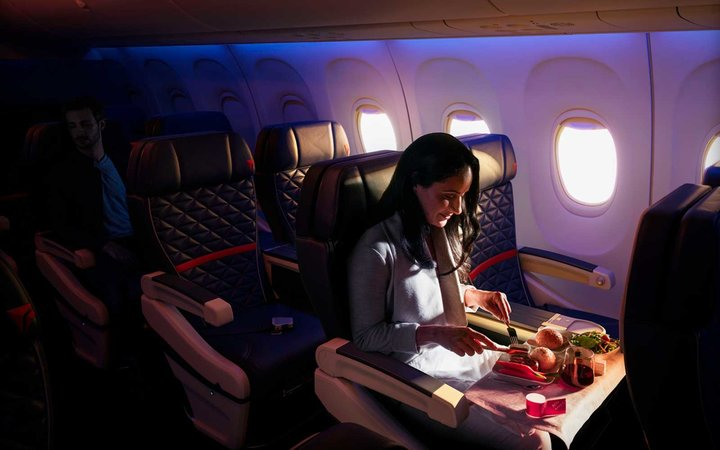 A woman dining in First Class on a Boeing 737-900ER