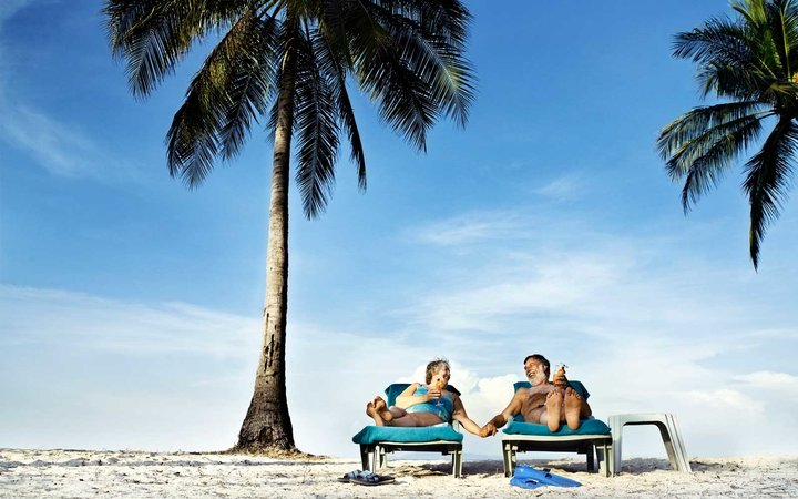 A middle aged English couple laying on beach chairs with cocktails in the tropics of Thailand.