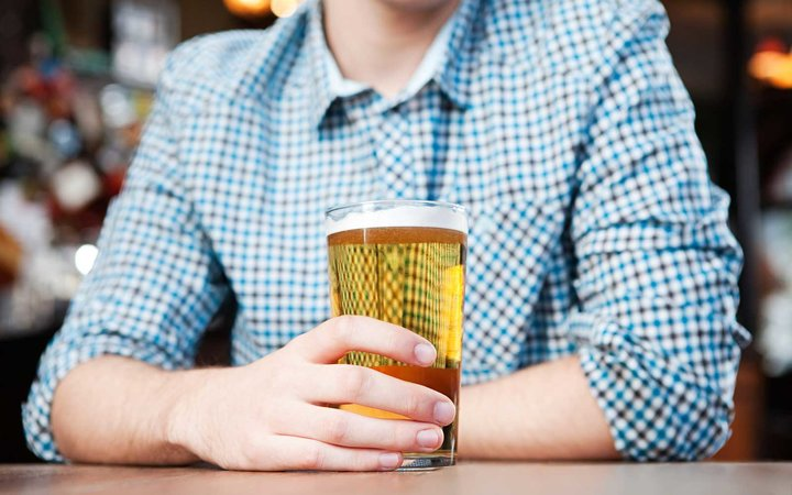 Young man in bar, mid section