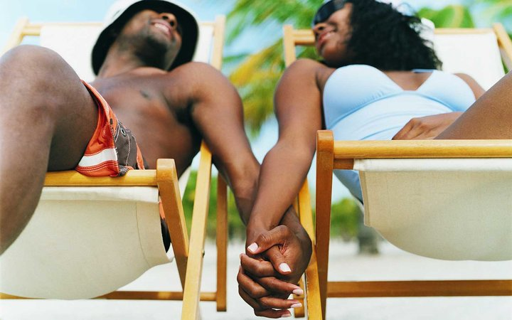 Couple Sitting on Deck Chairs, Holding Hands on the Beach