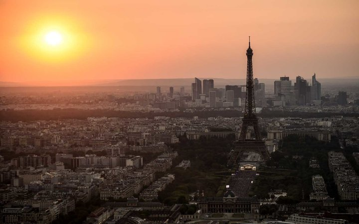 This picture taken from the panoramic observatory of the Montparnasse Tower (Tour Montparnasse) shows the sunset over Paris and the Eiffel Tower on July 14, 2018