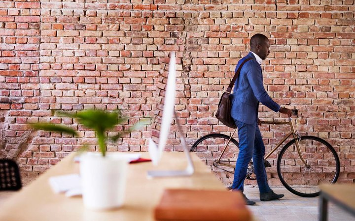 Businessman pushing bicycle in office