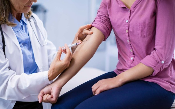 Doctor giving an injection to the patient