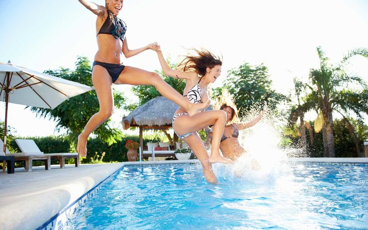 Women jumping into a swimming pool