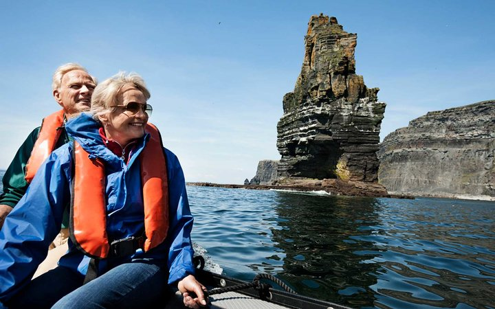 Senior man and woman wearing life jackets on an inflatable boat explore the ocean and the Cliffs of Moher, Ireland, United Kingdom