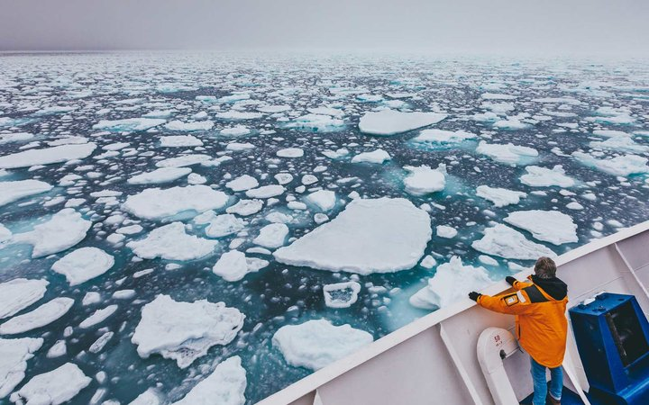 Quark Expeditions Ocean Explorer ship moving through ice in Antarctica