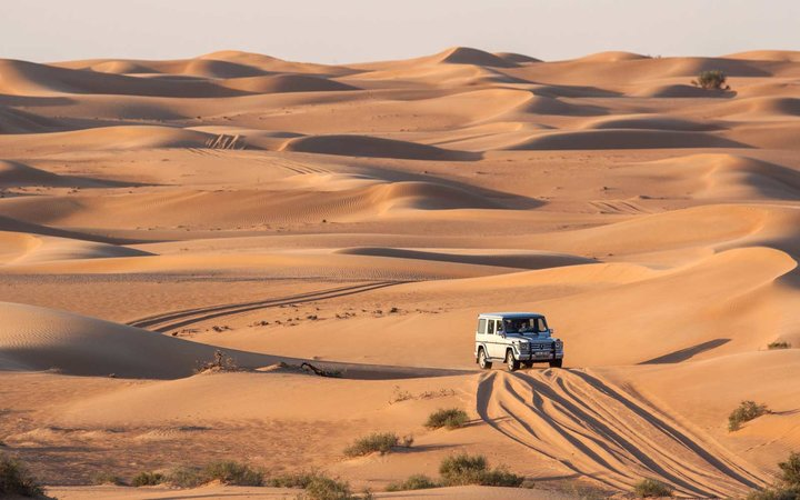 Mercedes SUV driving on the dunes of the Desert Conservation Area in Dubai, UAE