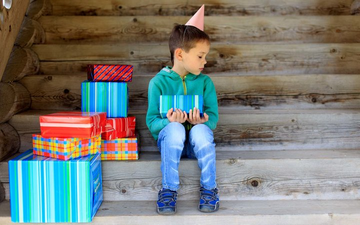one of the favorite and dear people did not come to the birthday to the little boy. child sits alone surrounded by gifts and sad looking an empty place next to him.