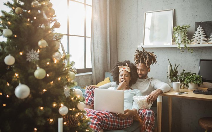 Young couple celebrating Christmas at home. Home is decorated with Christmas ornaments and lights, they sitting on sofa and using laptop