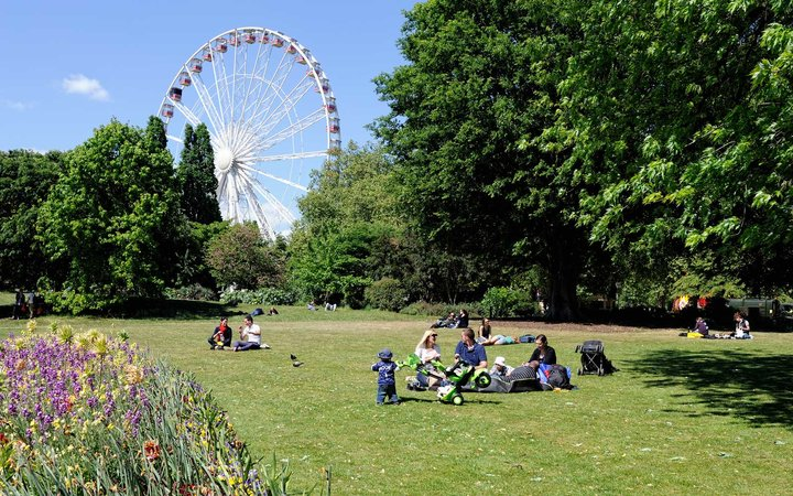 Couples and families spending the afternoon in the Hyde Park. The Hyde Park is one of the largest parks in central London and a popular location for leisure activities.