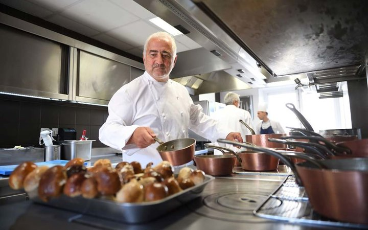 French chef Guy Savoy cooks in the kitchen of his Michelin three-starred restaurant  Restaurant Guy Savoy