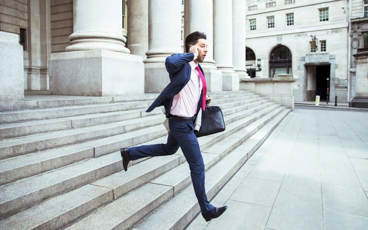 Businessman on cell phone running on city staircase