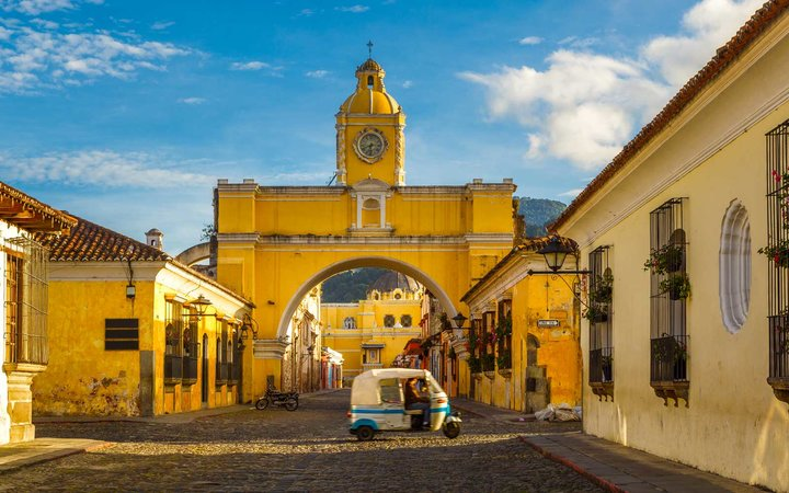 A tuk-tuk taxi passes in from of The Arch of Santa Catalina in Antigua, Guatemala.