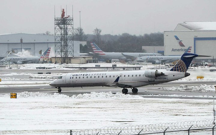 Airplanes taxi on the runway at Charlotte Douglas International Airport despite snowy conditions on Monday, Dec. 10, 2018