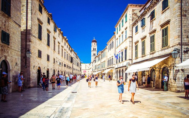 Tourists walk along paved stone streets of old city of Dubrovnik on warm sunny day, Dubrovnik, Croatia.