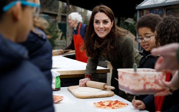 Catherine, Duchess of Cambridge speaks with children and helps makes pizza as she visits Islington Community Garden