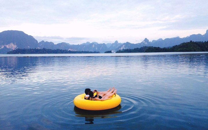 Couple On Inflatable Ring At Lake Against Sky