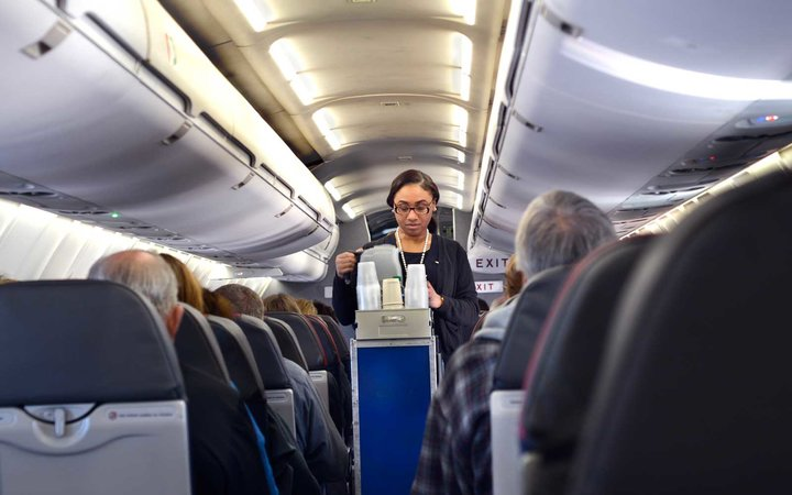 American Airlines flight attendant doing cabin service