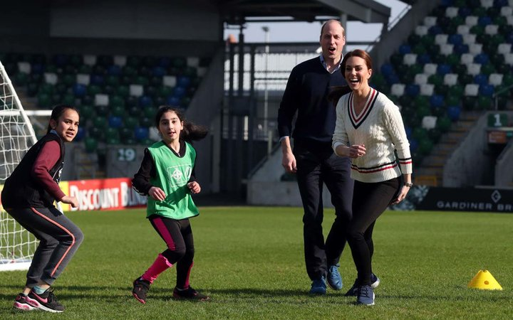 Prince William Duke of Cambridge and Catherine, Duchess of Cambridge, play football during a visit the National Stadium in Belfast, home of the Irish Football Association