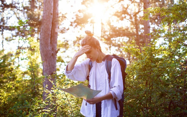 Woman in woods looking at a map