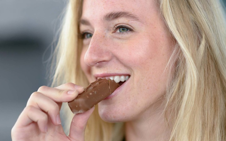Close-Up Of Smiling Young Woman Eating Chocolate