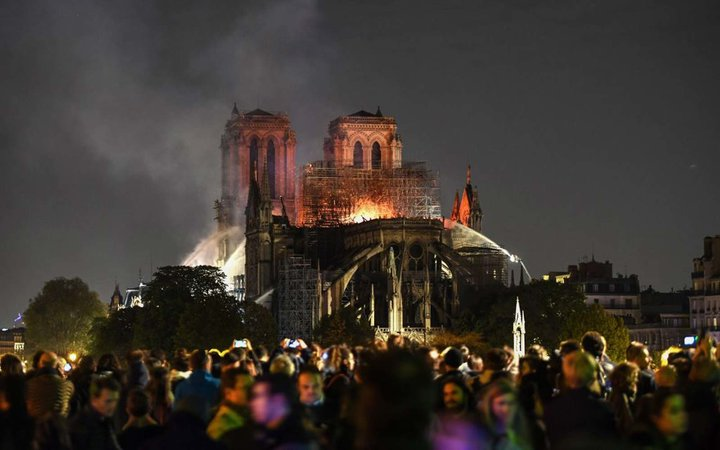 Bystanders look on as flames and smoke are seen billowing from the roof at Notre-Dame Cathedral in Paris