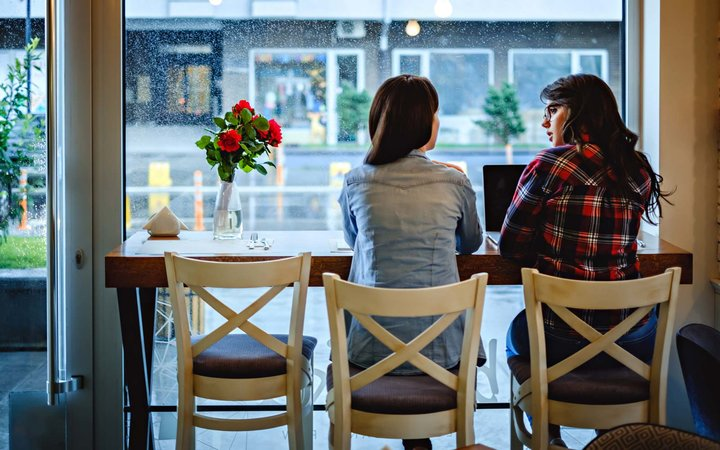 Girls talking in front of laptop at the cafe