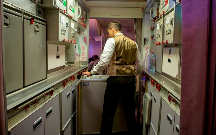 A cabin crew member moves carts in the galley.