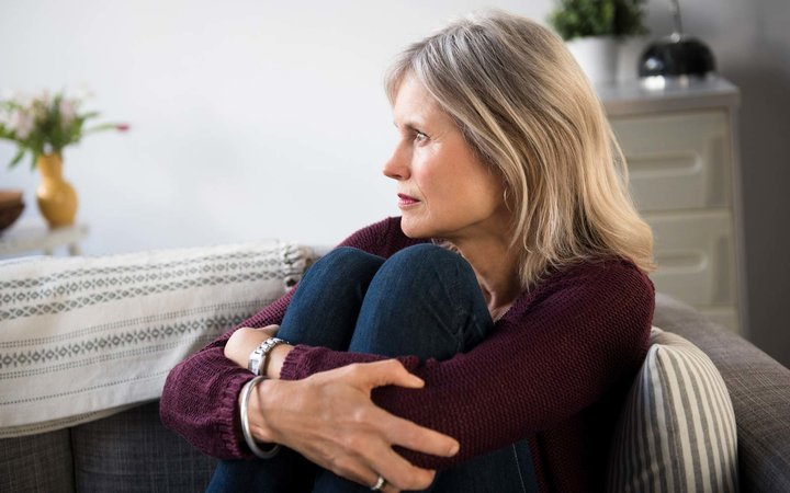 Worrying Caucasian woman hugging legs