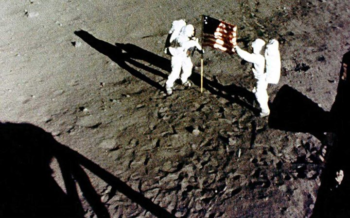 Neil Armstrong and Buzz Aldrin raise the American Flag on the Moon