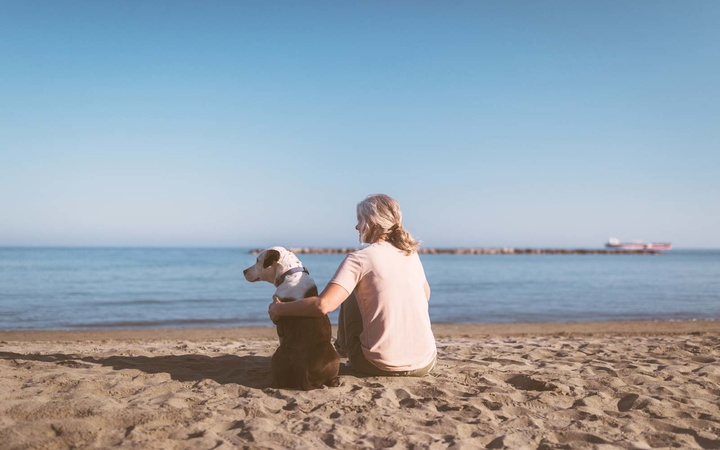 Mature woman with gray hair relaxing on beach with dog