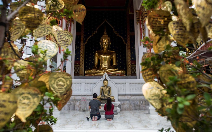 A couple prays at the Wat Saket temple, better known as   Golden Mount  , in Bangkok