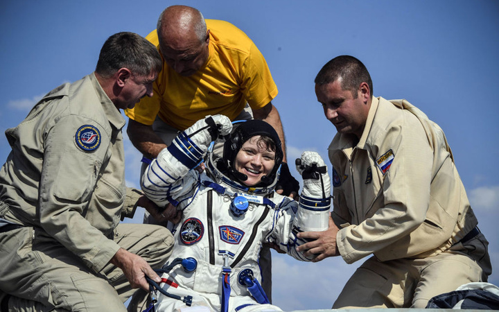 Ground personnel help NASA astronaut Anne McClain to get out of the Soyuz MS-11 capsule shortly after landing in a remote area outside the town of Dzhezkazgan