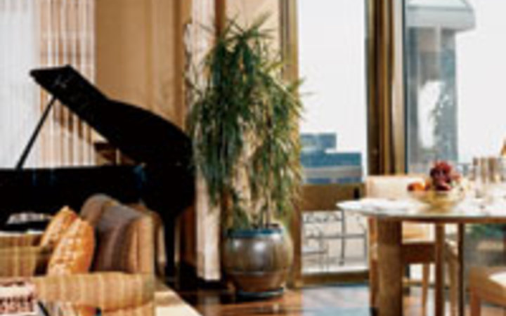 Morgan & Owens A living room in one of the Four Seasons' Presidential Suites, with baby grand piano.