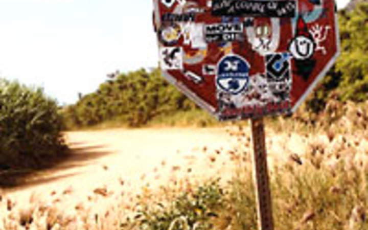 Tammy Kennedy & Brett Panelli Stickers adorn a stop sign near Polihale Beach