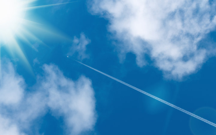 Airliner with vapour trail heading for the sun