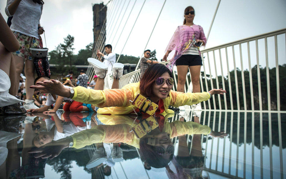 A woman splays out on a glass panel on the glass bridge.