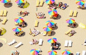 Aerial view of beach sunbathers summer umbrella sun