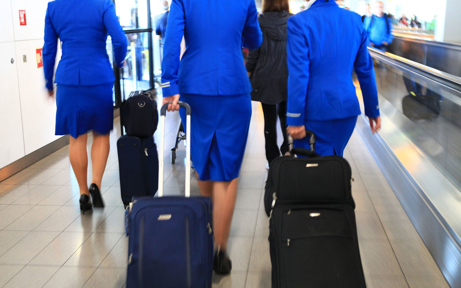 CRF7KW KLM royal dutch airlines flight attendants walking through airport terminal carrying pull rod case