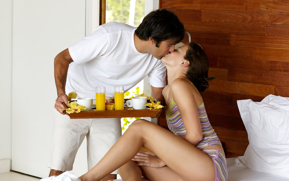 Man holding breakfast tray and kissing to woman on bed