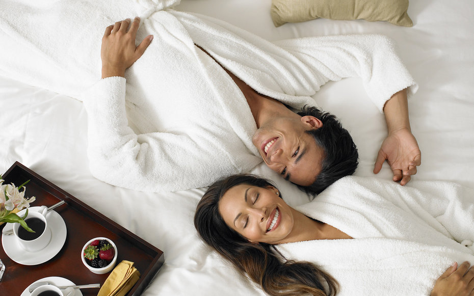 Couple in white bathrobes lying on bed, breakfast tray on side