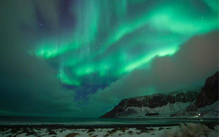 Northern lights ( aurora borealis ) illuminated the sky over the snow covered beach of Unstad, on Lofoten Island, Arctic Circle, on March 10, 2016.  