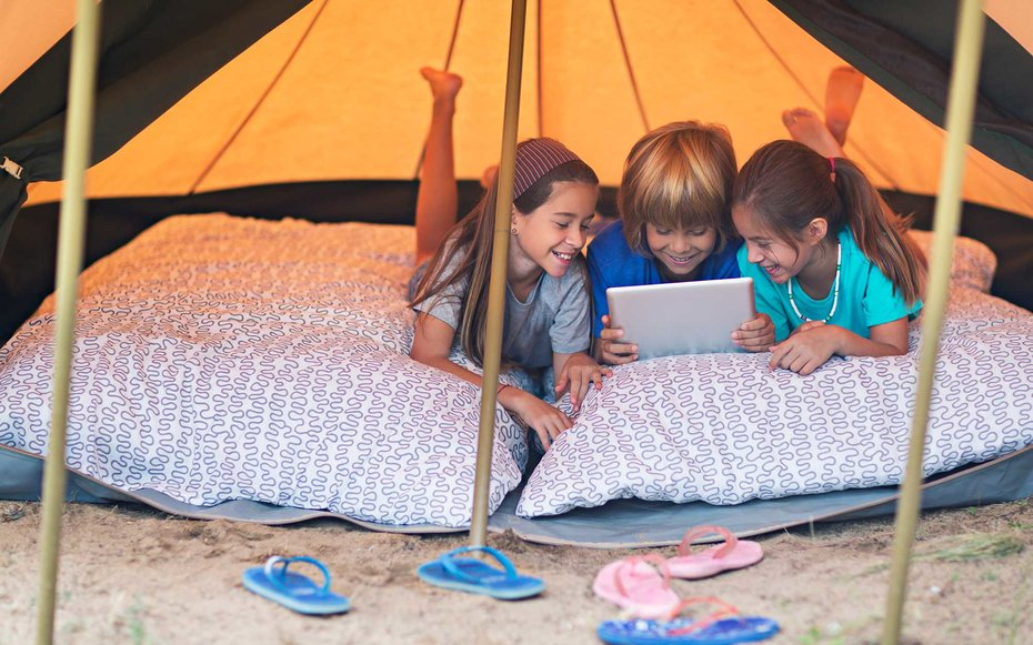 Three kids in the tent playing with the digital tablet.
