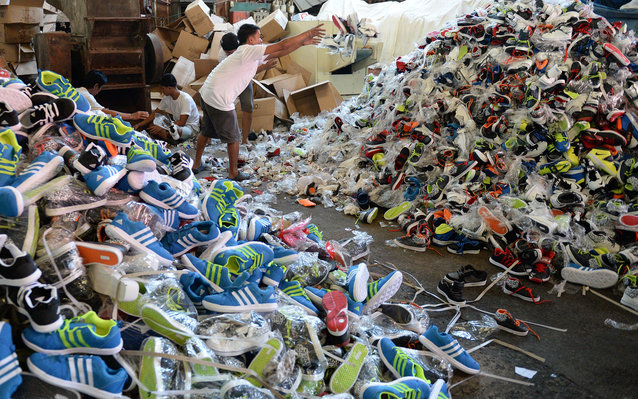 Workers for the Philippine customs bureau pile up thousands of confiscated counterfeit designer footwear products at a custom's warehouse in Manila on February 24, 2015. The fake footwear, which was smuggled into the country last year from China which off
